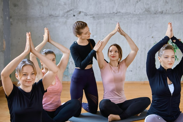 Entrenador ayudando a mujeres practicando meditación en el pasillo.