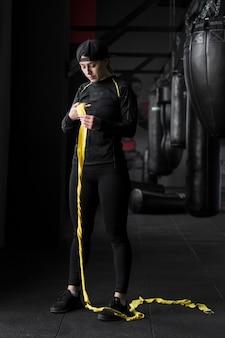 Entrenador boxer femenino con cordón elástico en el gimnasio.