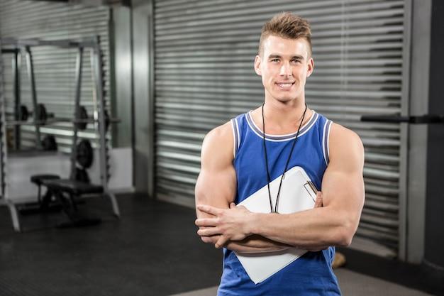 Entrenador confiado de pie con portapapeles en el gimnasio de crossfit