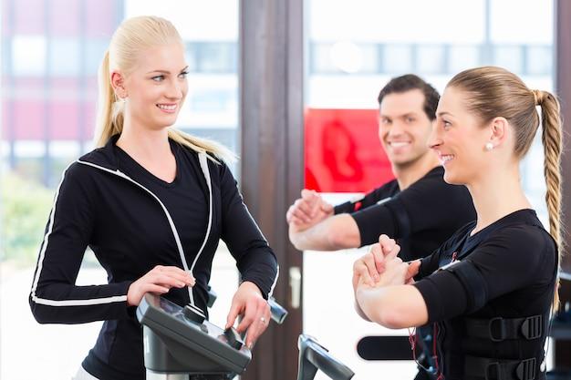 Entrenador dando entrenamiento ems a pareja.