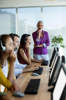 Entrenador ejecutivo de servicio al cliente supervisando a su equipo en la oficina