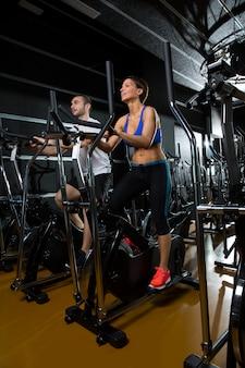 Entrenador elíptico walker hombre y mujer en el gimnasio negro