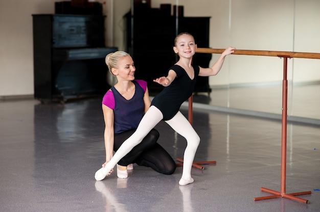 El entrenador le enseña a la niña cómo estirar la coreografía