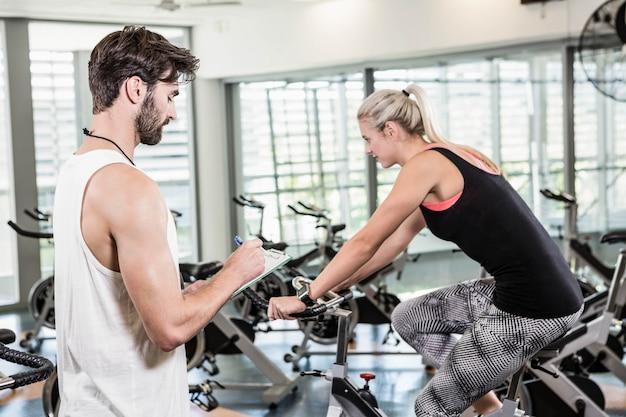 Entrenador escribiendo en el portapapeles y una mujer usando una bicicleta de ejercicios en el gimnasio