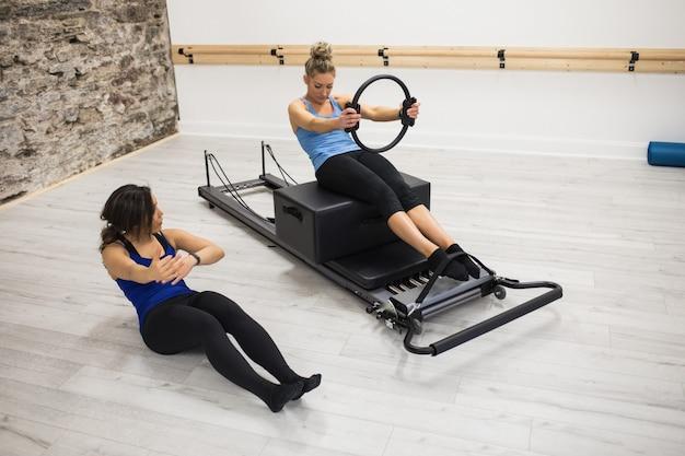 Entrenador femenino ayudar a la mujer a hacer ejercicio con anillo de pilates