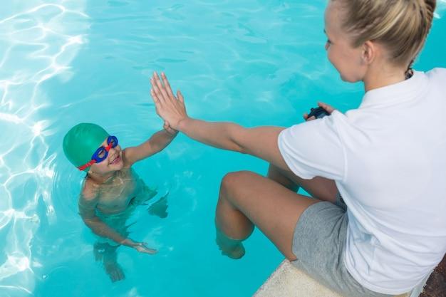 Entrenador femenino dando cinco al niño