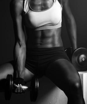 Entrenador de fitness chica afroamericana con pesas haciendo ejercicios
