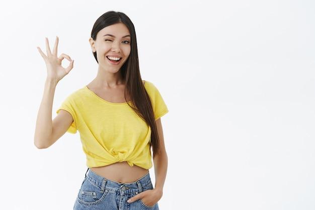 Entrenador de fitness femenino atractivo asegurando que ayudará a guiñar con alegría mostrando un gesto bueno o excelente con los dedos levantados
