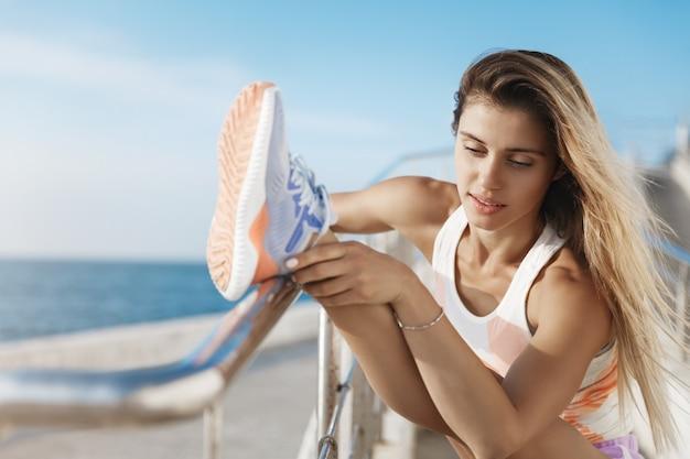 Entrenador de fitness femenino bronceado caucásico hermoso activo levantando la barra del muelle de la mano