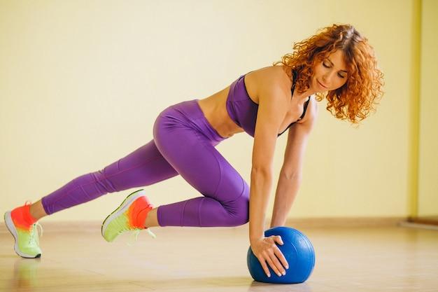 Entrenador de fitness de mujer con bola
