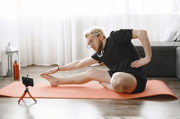 Entrenador de fitness o blogger de vídeo haciendo estiramientos. el hombre se está filmando a sí mismo con la cámara del teléfono inteligente en casa.