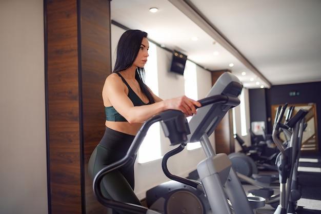 Entrenador de fitness trabajando en la máquina de paso y mostrando su figura en un traje deportivo