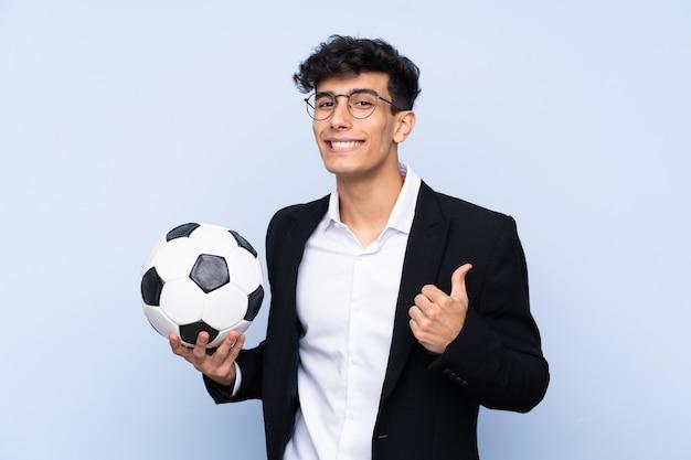Entrenador de fútbol argentino sobre una pared azul aislada con los pulgares hacia arriba porque algo bueno ha sucedido