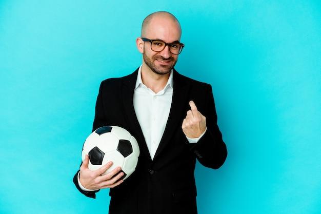 Entrenador de fútbol caucásico joven aislado sobre fondo blanco apuntando con el dedo como si invitara a acercarse.
