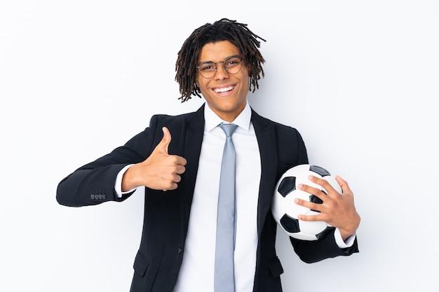 Entrenador de fútbol sobre una pared blanca aislada con los pulgares hacia arriba porque algo bueno ha sucedido