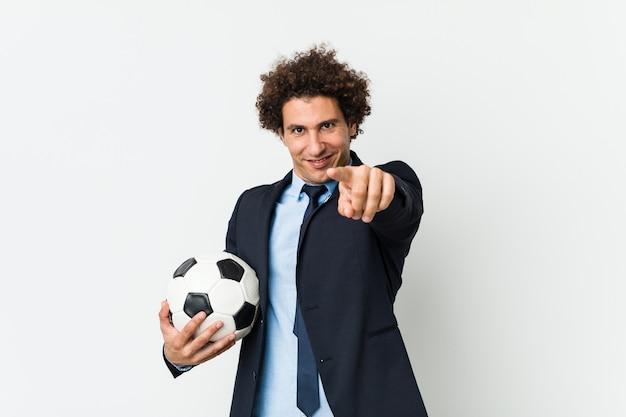 Entrenador de fútbol sosteniendo una bola alegre sonrisas apuntando al frente.