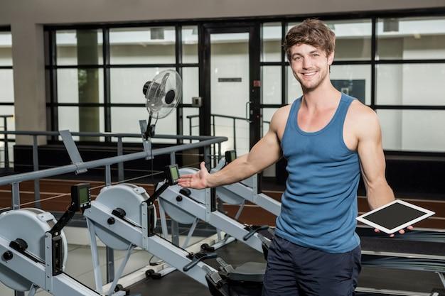 Entrenador de gimnasio feliz sosteniendo una tableta digital