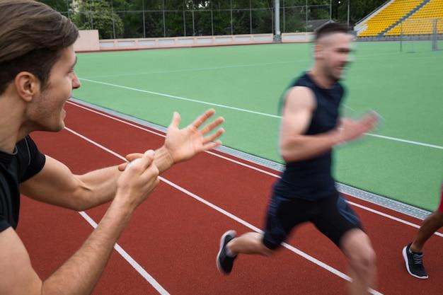 Entrenador gritando cerca de hombres jóvenes atletas multiétnicos