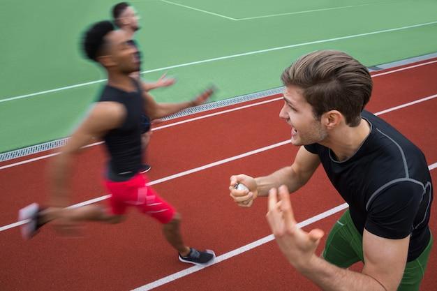 Entrenador gritando cerca de jóvenes atletas multiétnicos hombres corren