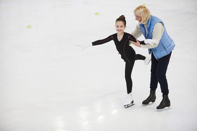 Entrenador helping girl patinaje artístico