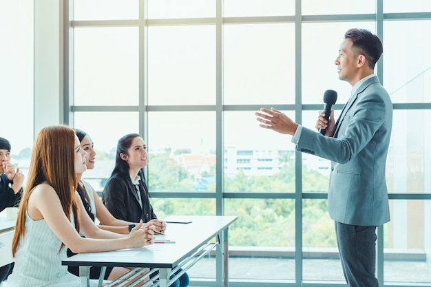 Entrenador de hombres de negocios asiáticos dando presentación