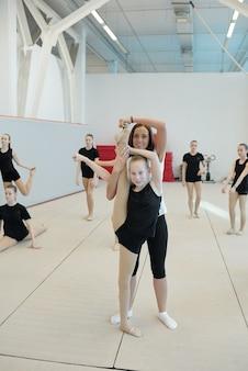 Entrenador joven sonriente de pie detrás de la niña y apuntando sus dedos de los pies mientras ella hace split vertical en la clase de porristas en la escuela