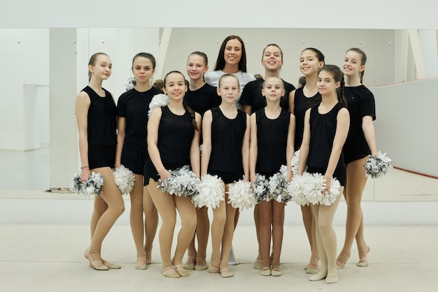 Entrenador joven sonriente posando con el equipo de chicas porristas en el pabellón de deportes