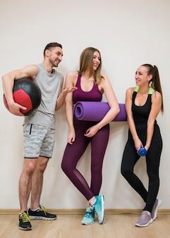 Entrenador junto con mujeres en el gimnasio