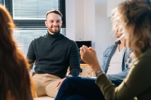 Entrenador de líder de equipo masculino feliz contando y discutiendo nuevas ideas con un equipo empresarial multirracial creativo, durante la lluvia de ideas. colega riendo sentados en círculo en la oficina tras un debate informal