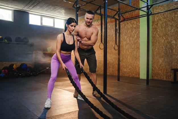 El entrenador masculino profesional enseña a la mujer joven caucásica a hacer el ejercicio correcto de la cuerda de batalla. mujer deportiva en entrenamiento intenso bajo el control del entrenador masculino en el gimnasio moderno negro lleno de luz solar.
