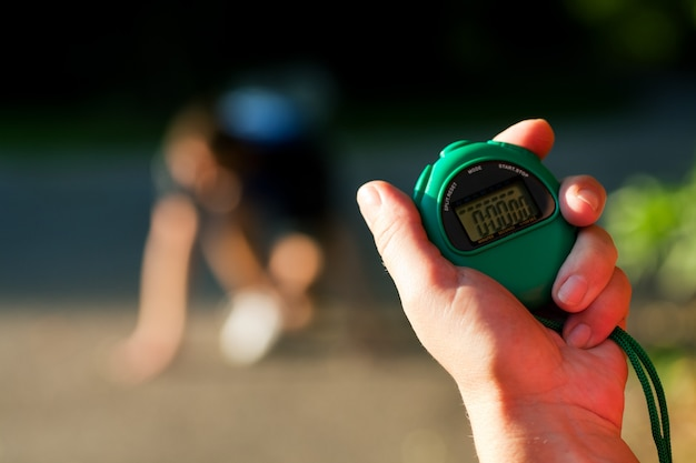 Entrenador midiendo el tiempo del corredor