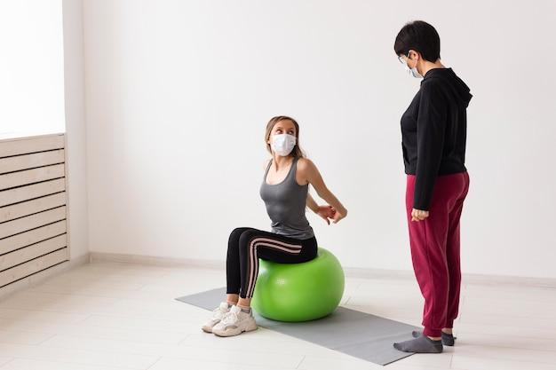 Entrenador mostrando a mujer cómo usar una pelota de fitness