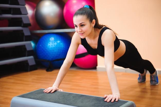 Entrenador de mujer atlética haciendo clase aeróbica con steppers. deporte