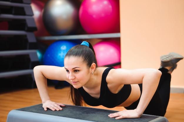 Entrenador de mujer atlética haciendo clase aeróbica con steppers.