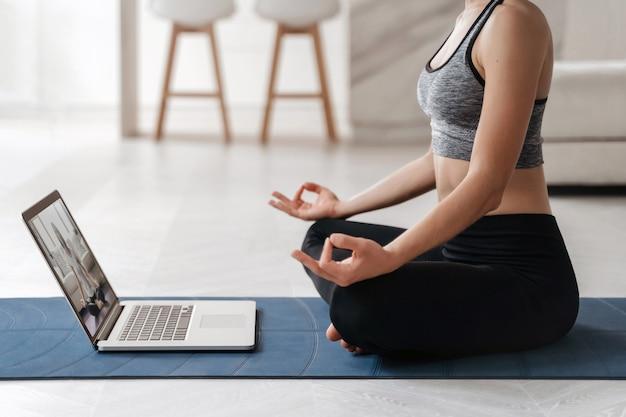Entrenador de mujer en forma de cerca tiene video de internet entrenamiento en línea de hatha yoga, practicando la postura de sukhasana