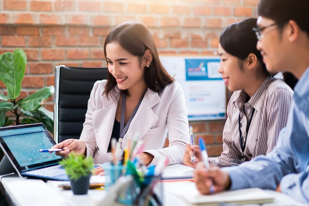El entrenador de una mujer de negocios está explicando algunas acciones en una computadora con un grupo