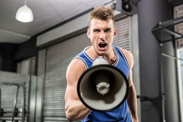 Entrenador muscular gritando en el megáfono en el gimnasio de crossfit