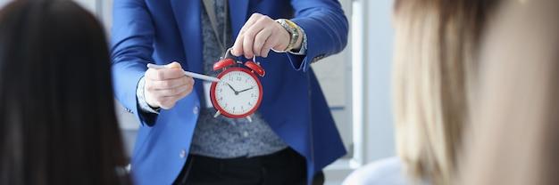 Entrenador de negocios que muestra el tiempo de los oyentes en primer plano del despertador rojo