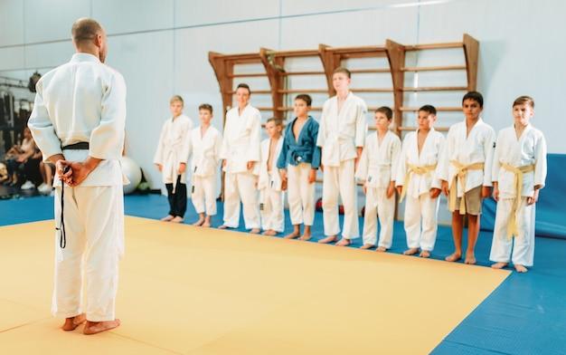Entrenador y niños pequeños, entrenamiento de judo para niños