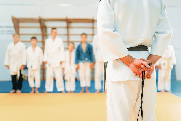 Entrenador y niños pequeños en kimono, entrenamiento de judo para niños. jóvenes luchadores en gimnasio, arte marcial para la defensa