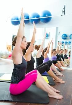 Entrenador personal aeróbico de pilates en una clase grupal de gimnasia.