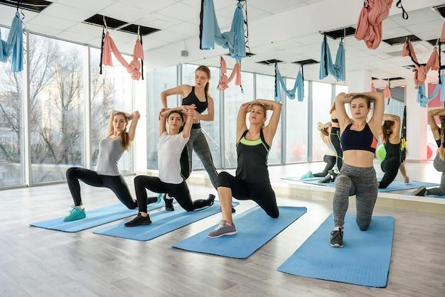 Entrenador personal ayudando a la mujer en el entrenamiento grupal en el gimnasio