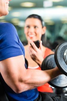 Entrenador personal en gimnasia y entrenamiento con mancuernas.