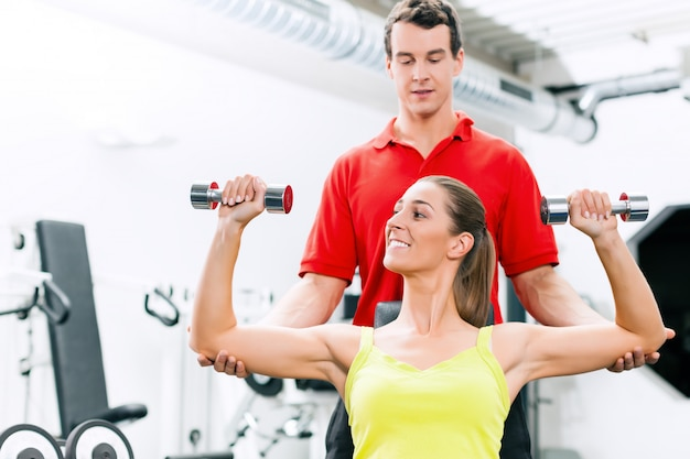 Entrenador personal en el gimnasio para una mejor forma física