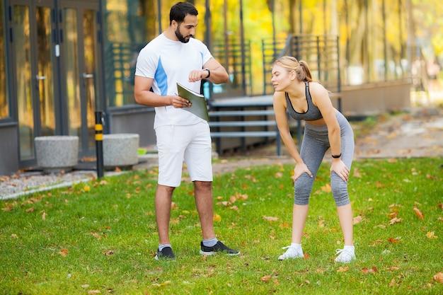 Entrenador personal masculino que muestra resultados a su clienta