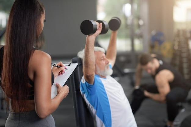 Entrenador personal que entrena a clientes en gimnasio.