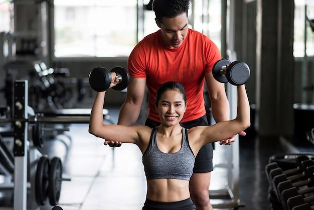 Entrenador personal que entrena con mancuernas a la mujer