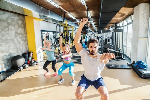 Entrenador personal que muestra ejercicios con pesas rusas a dos deportistas. interior de gimnasio.