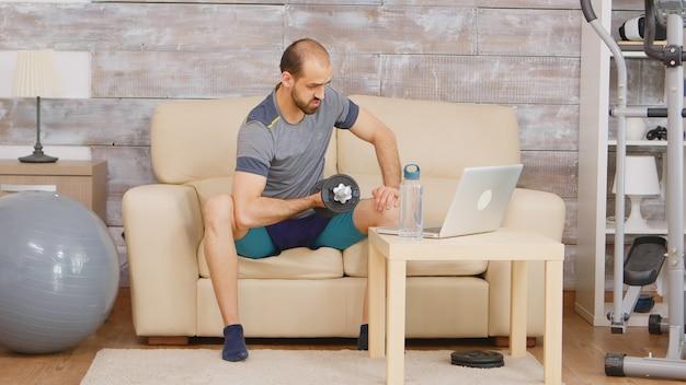 Entrenador personal que trabaja el músculo bíceps durante una videollamada con los clientes.