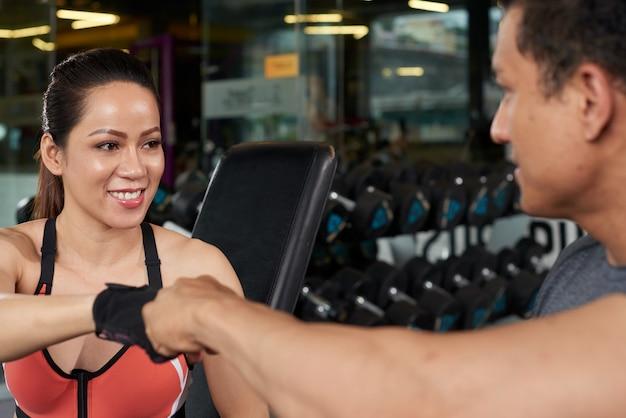 Entrenador personal saludando a una chica en forma en un gimnasio